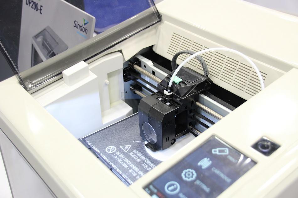 De 3Dwox DP200 printer van Sindoh. LInks de cartridge met het filament erin.